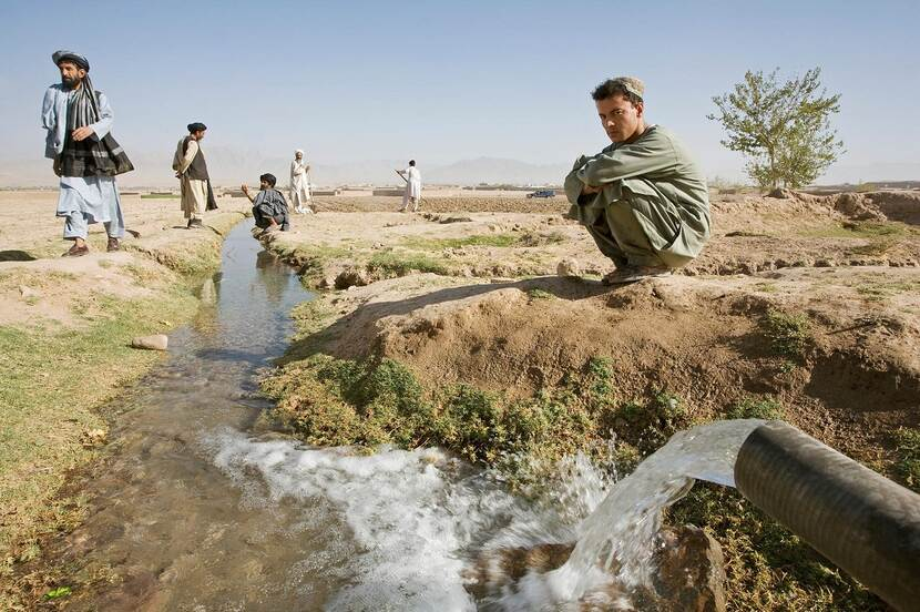A young Afghan man is crouching down next to an irrigation channel in Uruzgan